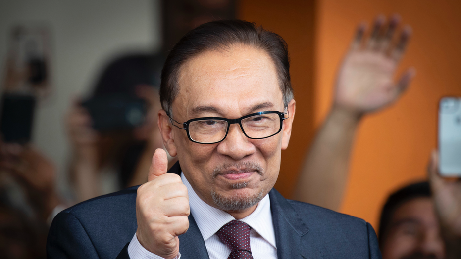 FILE - In this May 16, 2018, file photo, Anwar Ibrahim reacts to supporters as he leaves a hospital in Kuala Lumpur, Malaysia. Officials say Malaysia's prime minister-in-waiting Anwar will contest a by-election that will pave the way for his return to active politics. Lawmaker Danyal Balagopal Abdullah said Wednesday, Sept. 12, 2018, he has resigned as a member of Parliament in Port Dickson, a southern coastal town, to make way for Anwar's comeback. (AP Photo/Vincent Thian, File)