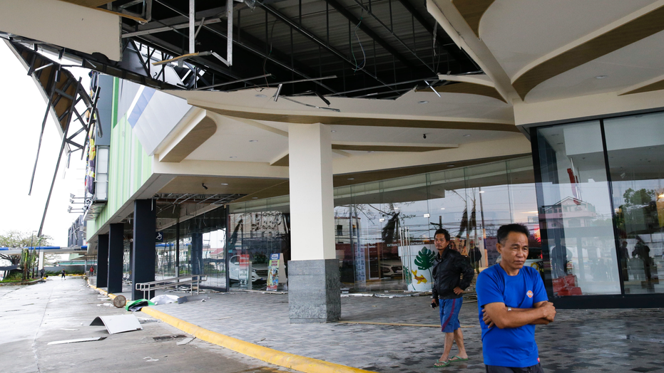 Residents stand beside a damaged portion of a mall due to strong winds from Typhoon Mangkhut as it barreled across Tuguegarao city in Cagayan province, northeastern Philippines on Saturday, Sept. 15, 2018. The typhoon slammed into the Philippines northeastern coast early Saturday, it's ferocious winds and blinding rain ripping off tin roof sheets and knocking out power, and plowed through the agricultural region at the start of the onslaught. (AP Photo/Aaron Favila)