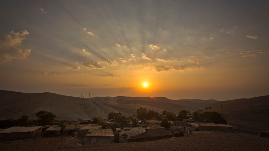 FILE - This Thursday, Sept. 13, 2018 file photo shows a sunrise over West Bank hamlet of Khan al-Ahmar. The Palestinian residents of Khan al-Ahmar cling to hopes that international pressure can save their strategically located West Bank hamlet from Israeli army bulldozers. After the West Bank hamlet lost its last legal protection against demolition late last week, Israeli forces could swoop in any day now to tear down the tiny desert community's few dozen shacks and schoolhouse made from recycled tires.(AP Photo/Majdi Mohammed)