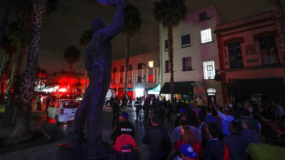 Curious onlookers gather on the perimeters of a crime scene after a shooting in Garibaldi Plaza in Mexico City.