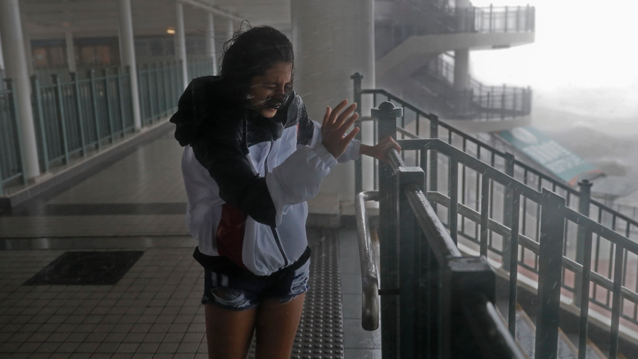 A girl stands against strong wind caused by Typhoon Mangkhut at a pier on the waterfront of Victoria Habour Hong Kong, Sunday, Sept. 16, 2018. Hong Kong and southern China hunkered down as strong winds and heavy rain from Typhoon Mangkhut lash the densely populated coast. The biggest storm of the year left at least 28 dead from landslides and drownings as it sliced through the northern Philippines. (AP Photo/Vincent Yu)