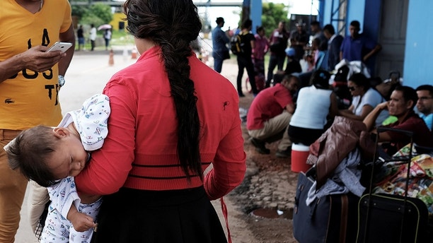 Venezuelans are pictured with their luggage before showing their passports or identity cards at the Pacaraima border control, Roraima state, Brazil November 16, 2017. Picture taken November 16, 2017. REUTERS/Nacho Doce - RC1BDA8FBDE0