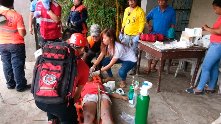 Red Cross Cebu Chapter Red Cross volunteers treat a victim after she was pulled out of her house that was struck by a landslide in Naga city Cebu province central Philippines on Thursday Sept. 20 2018. A Ph
