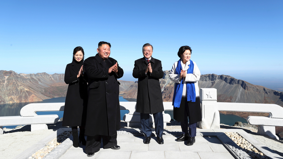 South Korean President Moon Jae-in, second from right, his wife Kim Jung-sook, right, North Korean leader Kim Jong Un and his wife Ri Sol Ju celebrate on Mount Paektu in North Korea, Thursday, Sept. 20, 2018. The leaders of the rival Koreas took to the road for the final day of their summit Thursday, standing on the peak of a beautiful volcano considered sacred in the North and a centerpiece of propaganda used to legitimize the Kim family's rule, their hands clasped and raised in a pose of triumph. (Pyongyang Press Corps Pool via AP)