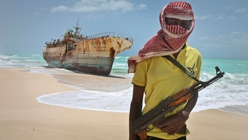 FILE - In this Sunday, Sept. 23, 2012 file photo, masked and armed Somali pirate Hassan stands near a Taiwanese fishing vessel washed ashore after the pirates were paid a ransom and the crew were released in the once-bustling pirate den of Hobyo, Somalia. Pirates have hijacked an oil tanker off the coast of Somalia, Somali officials and piracy experts said Tuesday, March 14, 2017, in the first hijacking of a large commercial vessel there since 2012. (AP Photo/Farah Abdi Warsameh, File)