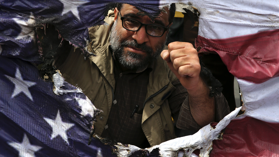 FILE - In this May 11, 2018 file photo, an Iranian protestor clenches his fist behind a burnt representation of the U.S. flag during a protest over U.S. President Donald Trump's decision to pull out of the nuclear deal with world powers, in Tehran, Iran. Ahead of the 40th anniversary of Iran's Islamic Revolution, the country's government is allowing more criticism to bubble up to the surface.