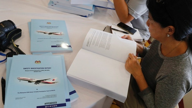 Copies of the final investigation report on missing flight MH370 are offered to the media in Putrajaya, Monday, July 30, 2018. Malaysia issues a safety investigation report with detail analysis after a renewed search by a private U.S. firm for missing Flight 370 in the southern Indian Ocean ended two months ago without finding the wreckage. The plane disappeared in March, 2014 with 239 people on board while flying from Kuala Lumpur to Beijing.(AP Photo/Vincent Thian)