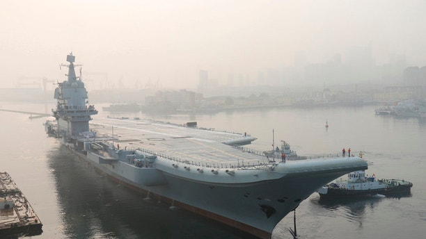 "FILE - In this May 13, 2018, file photo provided by China's Xinhua News Agency, China's indigenous aircraft carrier lifts anchor in Dalian in northeast China's Liaoning Province. The Philippines says it is taking ""appropriate diplomatic action"" to protect its South China Sea territorial claims, after China landed bombers on one of the islands it controls. China's first entirely home-built aircraft carrier completed a round of sea trials, putting it closer to possible deployment in the disputed waterway, while Chinese tourists in Vietnam sparked anger by wearing T-shirts showing their country's territorial claims, some of which overlap with Hanoi's. (Li Gang/Xinhua via AP, File)"
