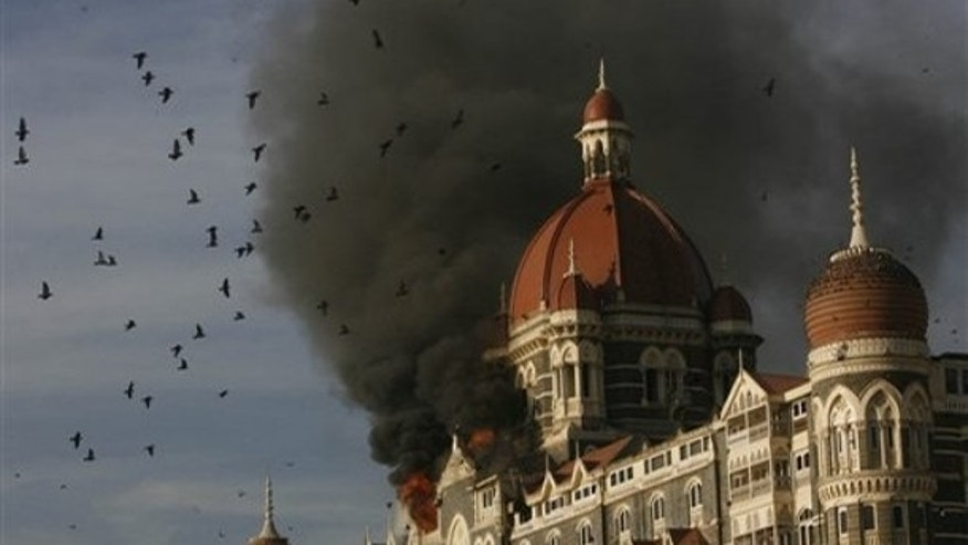 ** FILE ** In this Nov. 27, 2008 file photo, pigeons fly as the Taj Hotel continues to burn during terror attacks in Mumbai, India. Indian Prime Minister Manmohan Singh said Tuesday, Jan. 6, 2009, that he did not believe the November Mumbai attacks gunmen were acting alone, and Pakistani state agencies must have had a hand in the attacks. A ruthless exchange from a transcript of phone calls Indian authorities say they intercepted during the attack were part of a dossier of evidence New Delhi handed Pakistan this week that it says definitively proves that the siege was launched from across the border. (AP Photo/Gautam Singh, File)