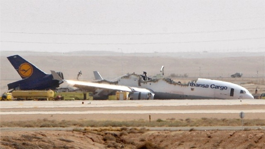 A man is seen standing on top of the wreckage of a Lufthansa cargo plane which caught fire and split in half as it was landing in the capital Riyadh, Saudi Arabia, Tuesday, July 27, 2010. The German pilot and co-pilot of Flight 8460, which was carrying about 90 tons of unspecified cargo, were lightly injured, an airport official said. (AP Photo)