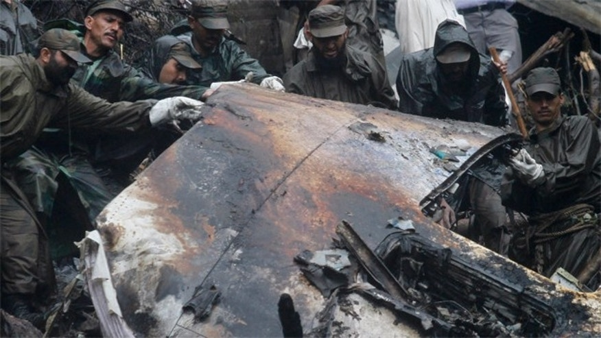 Pakistani army troops remove a piece of wreckage at the site of  Wednesday's deadly plane crash, in the mountains surrounding Islamabad, Pakistan on Thursday, July 29, 2010. The Airbus A321 operated by local carrier Airblue crashed into hills overlooking the country's capital, Islamabad, during stormy, monsoon weather, killing all 152 people on board. (AP Photo/Anjum Naveed)