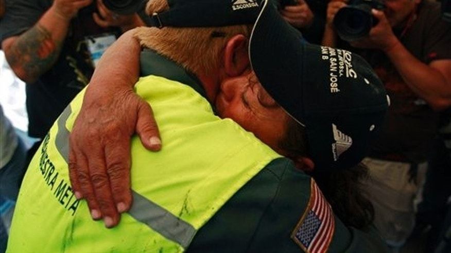Oct. 9: Jeff Hart, the T-130 drill operator from Denver, Colorado, left, embraces Elizabeth Segovia, sister of trapped miner Dario Segovia Rojo, at the San Jose Mine near Copiapo, Chile.