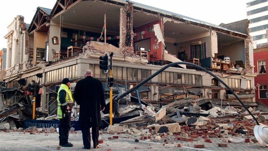 People stand outside a building damaged by a 7.4-magnitude earthquake in central Christchurch, New Zealand, early Saturday, Sept. 4, 2010. A powerful 7.4-magnitude earthquake struck much of New Zealand's South Island early Saturday. No tsunami alert was issued and there were no reports of injuries, but looters broke into some damaged shops in Christchurch, police said. (AP Photo/NZPA, David Alexander) ** NEW ZEALAND OUT **