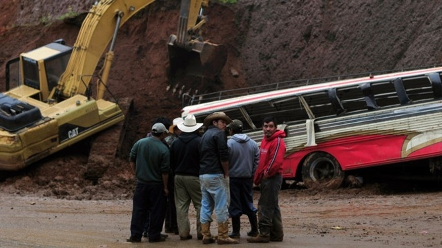 People stand in front of a bus partially covered by a landslide, due to heavy rains, on the Pan-American highway at Tecpan, Guatemala, Saturday Sept. 4, 2010. At least 12 passengers were killed and around 25 injured, rescue workers said. (AP Photo)