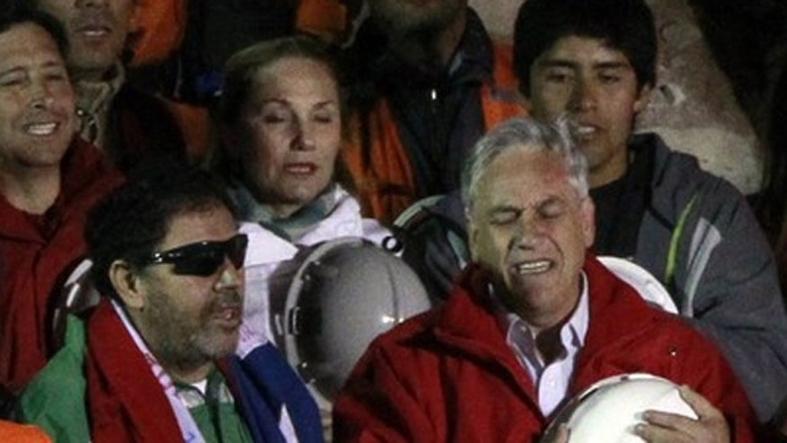 Chilean President Sebastian Pinera sings the national anthem with the last miner to be rescued, Luis Urzua, credited with organizing the miners to ration food and save themselves, at the end of the operation at the San Jose mine in Copiapo October 13, 2010. All of Chile's 33 trapped miners were rescued from deep underground in a special capsule on Wednesday as an extraordinary two-month survival story many call a miracle triggered wild celebrations.         REUTERS/Ivan Alvarado (CHILE - Tags: DISASTER POLITICS ENERGY)