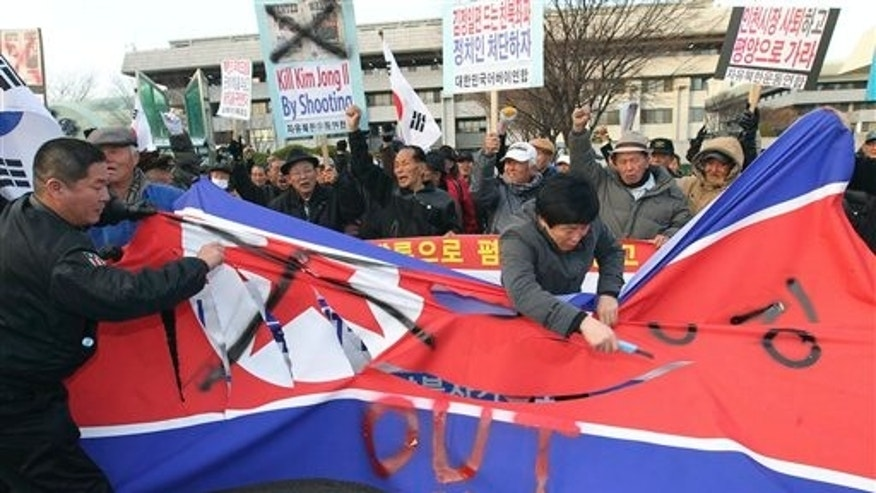 "South Korean protesters tear a North Korean flag with knives during a rally denouncing Tuesday's North Korean bombardment on a South Korean border island, in Incheon, South Korea, Saturday, Nov. 27, 2010. The United States and South Korea are pushing ahead with joint military drills Sunday even as North Korea calls the exercises an ""unpardonable provocation"" that drive the Koreas closer toward war. (AP Phoito/Yonhap, Ha Sa-hun)  KOREA OUT"