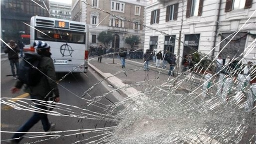 Demonstrators are seen through a bus smashed window during clashes in Rome, Tuesday, Dec. 14, 2010. Outside parliament, thousands of demonstrators marched, smashed shop windows, destroyed bank ATMs and set at least three vehicles on fire. At one point they even entered a bank, prompting staffers to try to barricade themselves inside. Police fired tear gas as the protesters neared Berlusconi's residence. Premier Silvio Berlusconi won back-to-back votes of confidence in the Italian parliament Tuesday to survive one of the toughest tests of his political life. But he was left with a razor-thin majority that will make it hard for him to govern effectively. (AP Photo/Pier Paolo Cito)