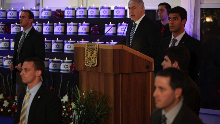 Surrounded by security, Israeli Prime Minister Benjamin Netanyahu, center, speaks during a ceremony for the victims of last month's massive Carmel forest fire, in Kibbutz Beit Oren, northern Israel, Wednesday, Jan. 5, 2011. Angry relatives forced Netanyahu to stop his speech at a ceremony honoring 42 Israelis killed in a huge forest fire last month. Family members shouted that he was responsible for the disaster. Others directed their anger at Interior Minister Eli Yishai, who was escorted out of the hall.  (AP Photo/Oded Balilty, Pool)
