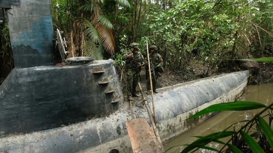Soldiers stand on a semi-submersible vessel in Timbiqui, southwestern Colombia, Monday, Feb. 14, 2011. The vessel was seized from drug traffickers during an operation Monday, authorities said. (AP Photo/Christian Escobar Mora)