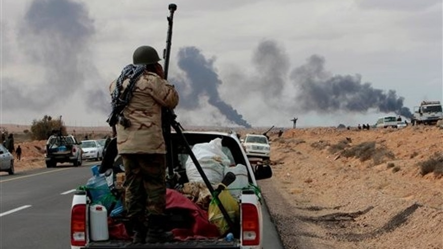 Anti-Libyan Leader Moammar Gadhafi rebel, stands behind his anti-aircraft machine gun as smokes rises from shell impacts in the distance during fighting against pro-Moammar Gadhafi forces, in Sedra, eastern Libya, on Wednesday March 9, 2011. Gadhafi appeared to be keeping up the momentum he has seized in recent days in his fight against rebels trying to move on the capital, Tripoli, from territory they hold in eastern Libya. (AP Photo/Hussein Malla)