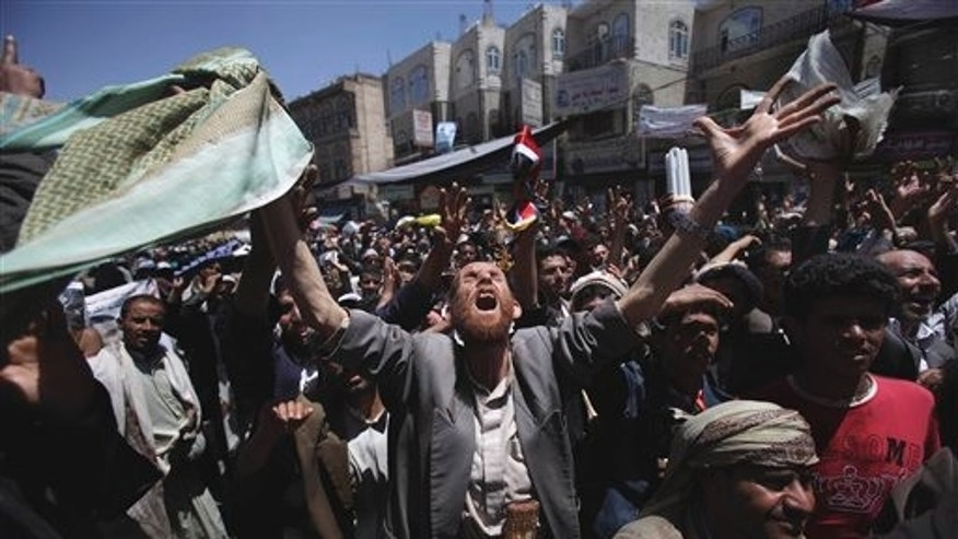 An anti-government protestor reacts during a demonstration demanding the resignation of Yemeni President Ali Abdullah Saleh, in Sanaa,Yemen, Wednesday, March 23, 2011. Yemen's parliament enacted sweeping emergency laws Wednesday after the country's embattled president asked for new powers of arrest, detention and censorship to quash a popular uprising demanding his ouster. (AP Photo/Muhammed Muheisen)