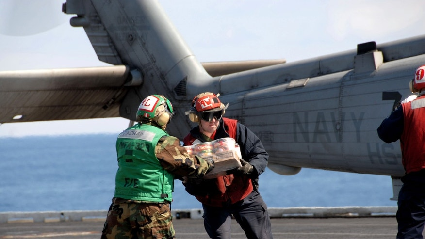 In this March 18, 2011 photo released by the U.S. Navy, sailors and Marines load food and humanitarian supplies onto a Sea Hawk helicopter aboard the aircraft carrier USS Ronald Reagan off the coast of Japan. The USS Ronald Reagan is off the coast of Japan providing humanitarian assistance to Japan after an earthquake and tsunami devastated the region. (AP Photo/U.S. Navy, Mass Communication Specialist 3rd Class Anthony Johnson)