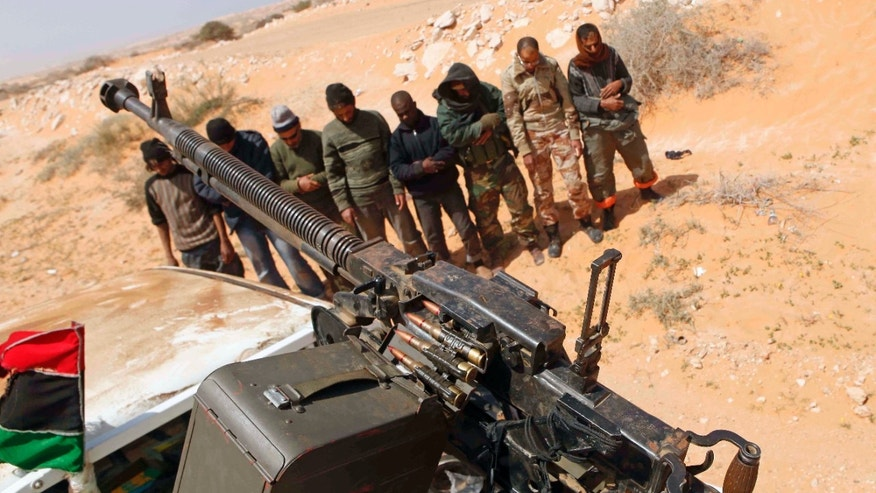 Libyan rebels pray some 120 km (75 miles) east of Sirte in eastern Libya,Monday, March 28, 2011.  Rebel forces on Monday fought their way to the doorstep of Moammar Gadhafi's hometown of Sirte, a key government stronghold guarding the road to the capital Tripoli. (AP Photo)