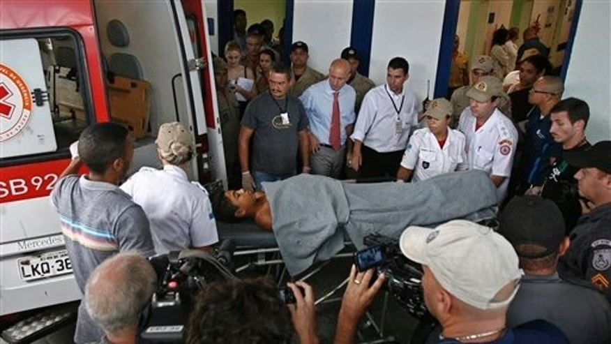 A boy who was wounded in a school shooting lies on a stretcher as he is put in an ambulance to be transferred from one hospital to another in Rio de Janeiro, Brazil, Thursday April 7, 2011.  A gunman opened fire at an elementary school in Rio de Janeiro on Thursday and killed at least 11 adolescents before killing himself. Earlier, police said at least 13 people died in the shooting, but Rio state Health Secretary Sergio Cortes said 10 girls and one boy were killed, along with the gunman. (AP Photo)