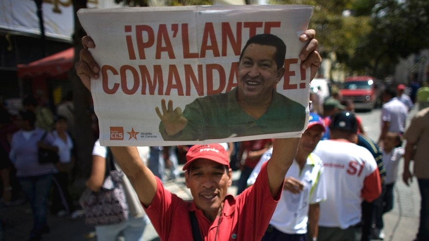 "A man celebrates the return of Venezuela's President Hugo Chavez, holding a poster bearing the president's image that reads in Spanish; ""Moving forward Commander,"" in Caracas, Venezuela, Monday July 4, 2011. Chavez returned to Venezuela from Cuba on Monday morning, stepping off a plane hours before dawn and saying he is feeling better as he recovers from surgery that removed a cancerous tumor. (AP Photo/Ariana Cubillos)"