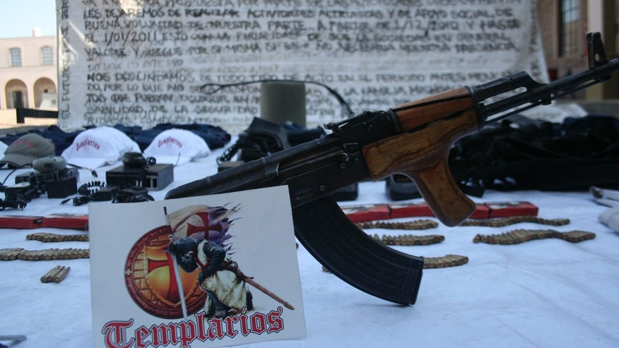 In this photo taken April 2, 2011, weapons, munitions, false police uniforms, communication equipment, a message to the government written on a large canvas  and paraphernalia allegedly belonging to the recently created Templar Knights drug cartel, are shown to the press after they were seized during a Mexican army operation in the city of Zitacuaro, Mexico. This was the first apparition of Templar Knight drug cartel logos since they announced their creation after they split from the La Familia cartel in March. (AP Photo)