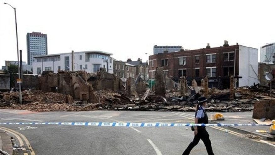 A police officers walks behind a cordon in front of Reeves Furniture showroom in Croydon, south London which was destroyed by fire in Monday's disturbances in the area Wednesday Aug. 10, 2011. The presence of thousands of extra police officers helped keep a nervous London quiet early Wednesday after three nights of rioting, but violence and looting flared in English cities including Manchester and Birmingham. (AP Photo/Gareth Fuller/PA Wire  UNITED KINGDOM OUT NO SALES NO ARCHIVE PHOTOGRAPH