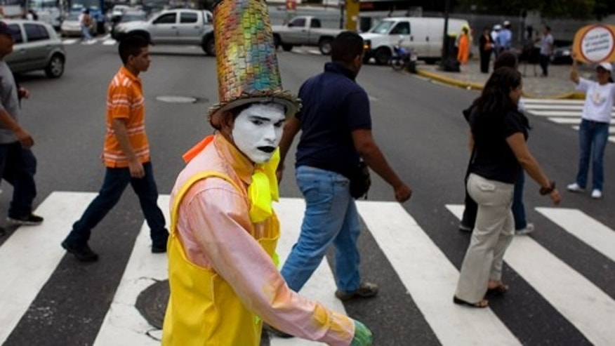A mime walks alongside pedestrians as they cross a street in Caracas, Venezuela, Friday Oct. 7, 2011. The mayor of the city's eastern district of Sucre has launched a unique program aimed to encourage civility among reckless drivers and careless pedestrians, putting 120 mimes at intersections to politely and silently scold violators. The campaign kicked off this week as mimes posted at busy intersections mocked people who jaywalked or acted brutish behind the wheel. (AP Photo/Ariana Cubillos)