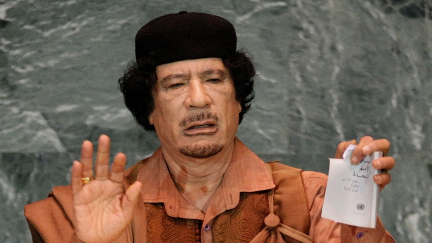 FILE - In this Sept. 23, 2009 photo, Libyan leader Moammar Gadhafi shows a torn copy of the UN Charter during his address to the 64th session of the United Nations General Assembly.    A U.S. official says Libya's new government has told the United States that Moammar Gadhafi is dead. The official said Libya's Transitional National Council informed U.S. officials in Libya of the development Thursday, Oct. 20, 2011.   (AP Photo/Richard Drew)