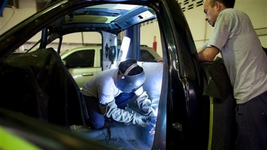 In this photo taken Nov. 18, 2011, men assemble a brand new armored car in Cagua, Venezuela. According to Horacio Zuniga, business manager of the Bogota-based glass manufacturer Glassek, Venezuela is the Latin American country with the biggest growth in sales of bullet-resistant windows. Venezuelans are coping with increasing numbers of abductions, robberies and killings, driven at least in part by ineffective law enforcement that allows the vast majority of crimes to go unsolved and unpunished.(AP Photo/Ariana Cubillos)