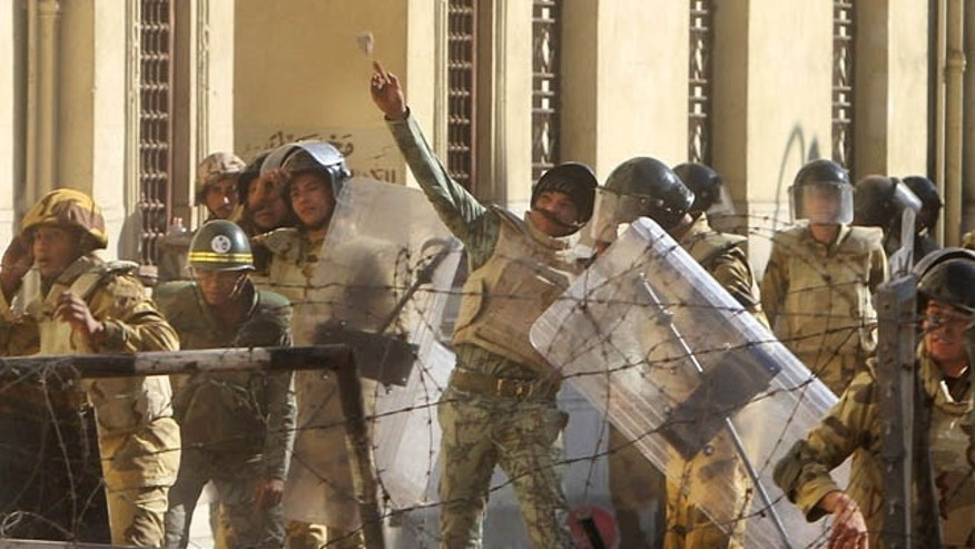 An Egyptian military solider throws a rock toward protesters near Tahrir Square in Cairo, Egypt, Sunday, Dec. 18, 2011. Troops and protesters are clashing for the third straight day in Cairo, pelting each other with rocks in skirmishes near parliament in the heart of the Egyptian capital. (AP Photo/Ahmed Ali)