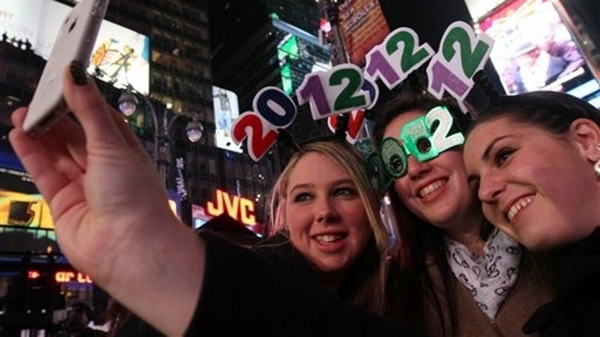 Samantha Mulhaul, left, and her cousin Stephanie Pignataro, center, and friend Haley Meltcher, all of New York state, take a picture of themselves shortly before midnight as they take part in the New Year's Eve festivities in Times Square, Saturday, Dec. 31, 2011, in New York. (AP Photo/Tina Fineberg)
