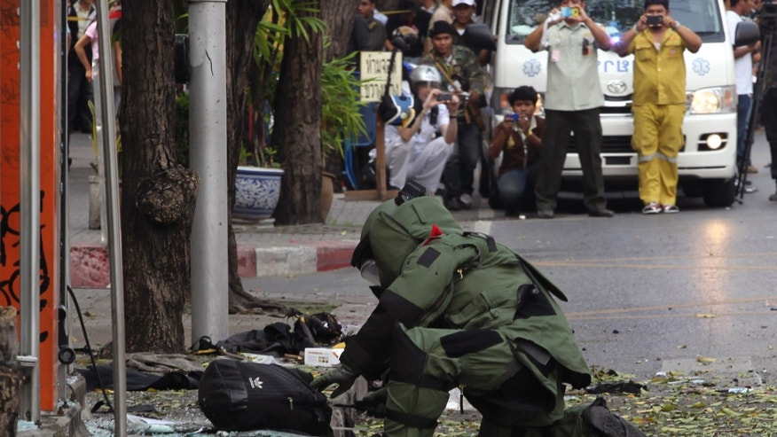 A Thai Explosive Ordnance Disposal (EOD) official examines a backpack that was left on the bomb site by a suspected bomber in Bangkok, Thailand Tuesday, Feb. 14, 2012. Thai police say two explosions have occurred in a Bangkok neighborhood. But it was not immediately clear what caused the blasts or wether there were an fatalities. (AP Photo/Apichart Weerawong)