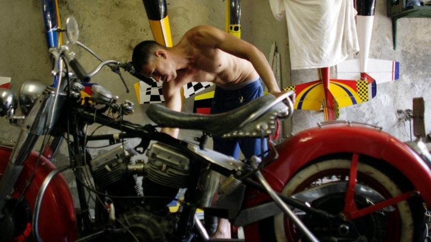 "Yaismer Escalona works on a Harley Davidson in Havana, Cuba, Friday April 13, 2012.  Cuban Harley Davidson owners and enthusiasts will gather this weekend for the island's first-ever national gathering in honor of the ""hog"" in the tourist resort city of Varadero. (AP Photo/Javier Galeano)"