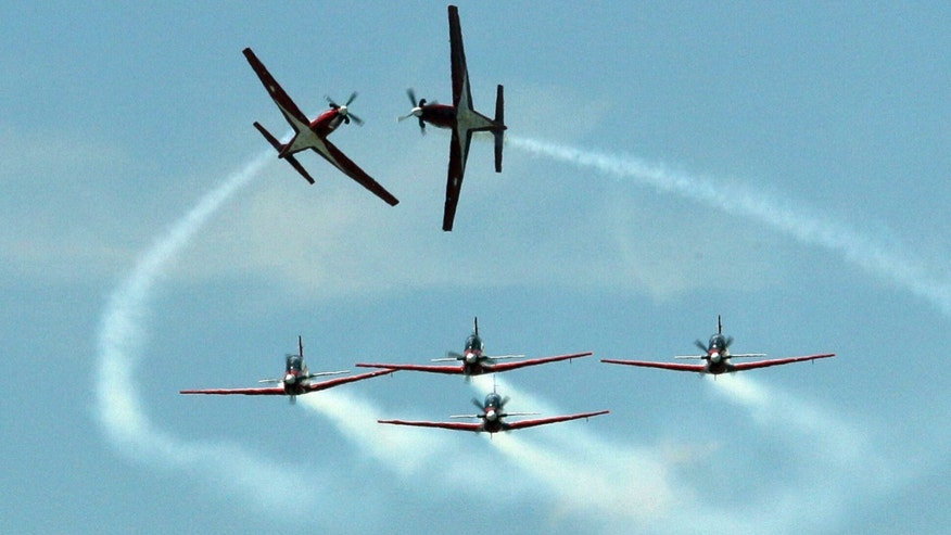 Indonesian flight demonstration team Jupiter KT1 performs aerobatic flight on Friday, June 29, 2012 in Bangkok ,Thailand, during 100th anniversary of Royal Thai Air Force. (AP Photo/Sakchai Lalit)