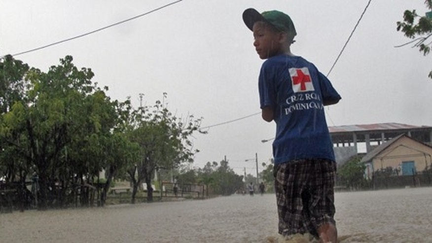Wearing a Dominican Red Cross t-shirt a kid walk thru a flooded street Cross after Tropical Storm Isaac hit in Barahona, Dominican Republic, Saturday, Aug. 25, 2012.  Forecasters said Isaac could dump as much as eight to 12 inches and even up to 20 inches on Hispaniola, which is shared by Haiti and the Dominican Republic, as well as produce a storm surge of up to 3 feet. (AP Photo/Ricardo Arduengo)