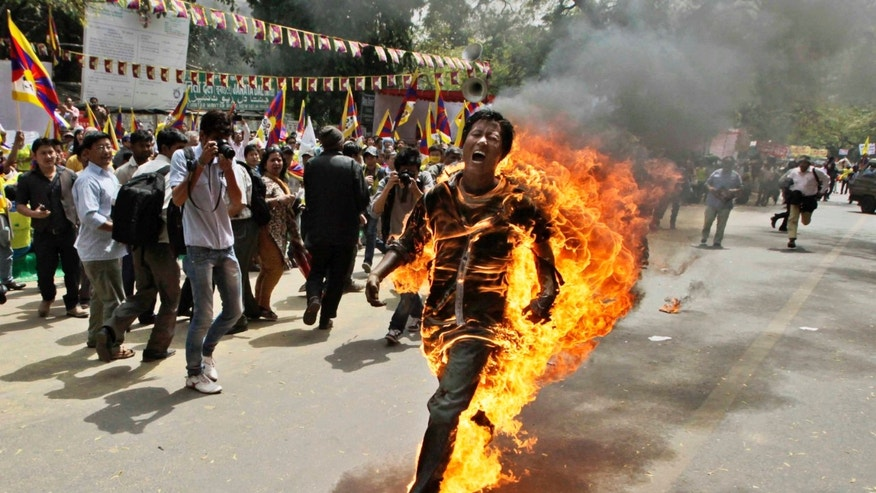 FOR USE AS DESIRED, YEAR END PHOTOS - FILE - In this March 26, 2012 file photo, Tibetan exile Jamphel Yeshi screams as he runs engulfed in flames after setting himself on fire at a protest in New Delhi, India, against Chinese President Hu Jintao's visit to India. Yeshi died two days later while hundreds of other activists were being held without charge before the president's arrival. Hu arrived in New Delhi for a summit with India, Russia, Brazil and South Africa. (AP Photo/Manish Swarup, File)