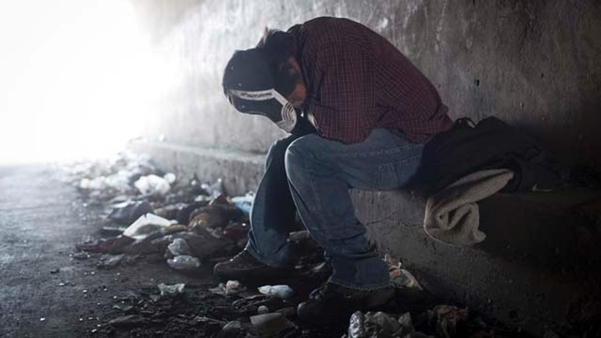 In this photo taken June 22, 2011, a homeless tries to rest inside a Tijuana River canal tunnel, in Tijuana, Mexico. During the day, deportees who find themselves in Tijuana look for work and flee Mexican police, who will jail them for not having papers, just like in the U.S. At night they take refuge in the canals, beneath bridges or in shacks, among drug addicts and people with mental health problems; a few feet from the rusty barrier that separates the country of their birth from the country where they worked years for a better life.  (AP Photo/Alejandro Cossio)