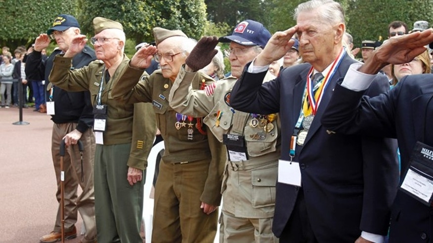 WW II U.S. veterans salute during the national anthems at a ceremony held at the Memorial of the Colleville American military cemetery, in Colleville sur Mer, western France, Thursday June 6, 2013, on the day of the commemoration of the 69th anniversary of the 1945 D-Day landings. From left: Melbert Hillert, 91, from Fresco, Texas,  Earl Tweed, 91, from Dallas, Texas, Robert Blatnik, 93 from Raleigh, Texas, Robert Bearden, 90, from Belton, Texas, and Joseph J. Turecky, 91, from Dallas, Texas.(AP Photo/Remy de la Mauviniere)