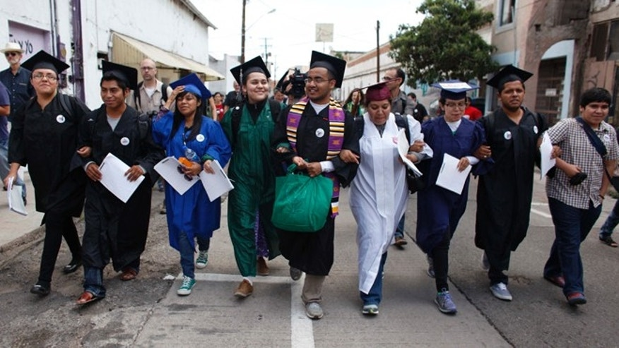"FILE - In this July 22, 2013 file photo, immigration rights activists, wearing their school graduation caps and gowns to show their desire to finish school in the U.S., march with linked arms to the U.S. port of entry where they planned to request humanitarian parole in Nogales, Mexico.  The activists, known as the ""Dream 9,"" were later arrested after attempting to cross the border. They were released from federal custody in Arizona on Wednesday, Aug. 7, 2013. (AP Photo/Samantha Sais, File)"