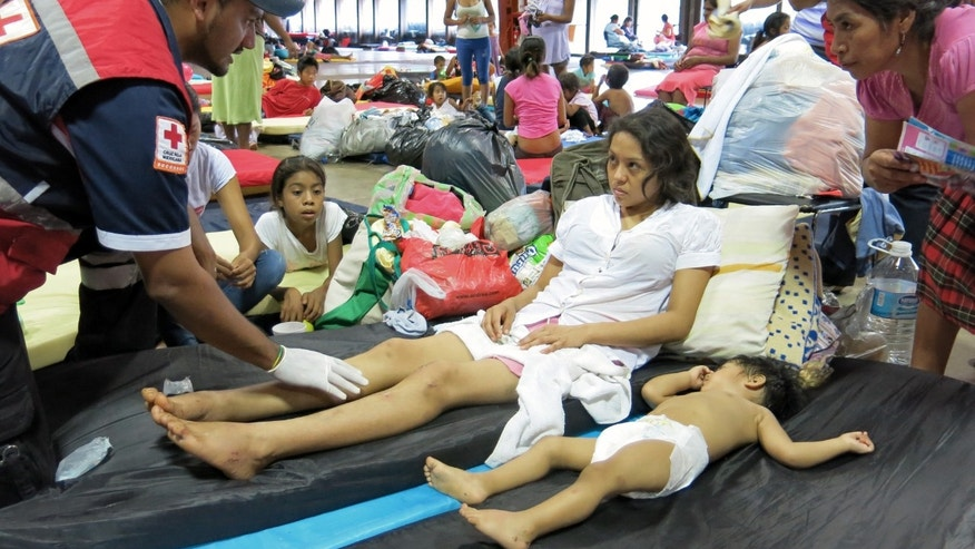 Nancy Gomez, 21, an injured resident of La Pintada, and her 1-year-old baby, receive medical attention in a shelter at the Convention Center in Acapulco, Mexico, Thursday, Sept. 19, 2013. Federal police rescued more than 300 people from La Pintada after it was hit by a landslide Monday afternoon, but officials said at least 58 people were missing and presumed dead. Gomez said that she heard a strange sound and went to look out the doorway of her family's house, her baby clutched in her arms. She saw the ground move, then felt a jolt from behind as her father tried to push her to safety. She never saw him again. (AP Photo/Michael Weissenstein)