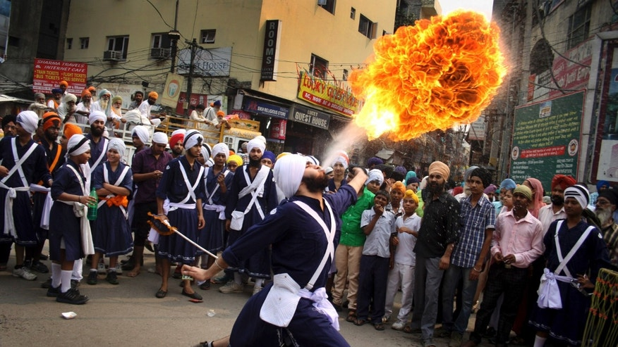 A Sikh youth performs an act of fire as he displays martial art skills during a religious procession on the eve of birth anniversary of Guru Ram Das in Amritsar, India, Tuesday, Oct. 8, 2013. Ram Das was the fourth of the ten gurus of Sikhism. (AP Photo/Sanjeev Syal)
