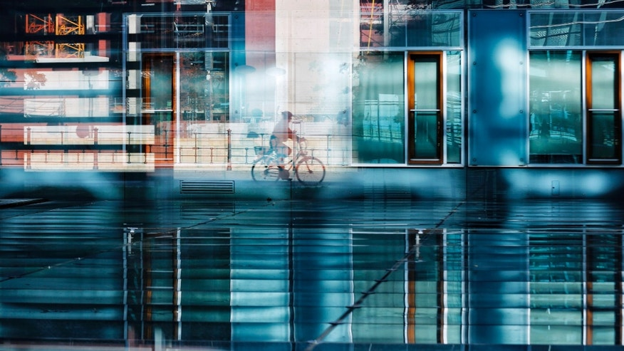 A person rides with a bicycle alongside the river Spree as it is photographed trough multiple reflections of windows at a courtyard of a parliament office building in Berlin Monday, Oct. 14, 2013. AP Photo/Markus Schreiber)