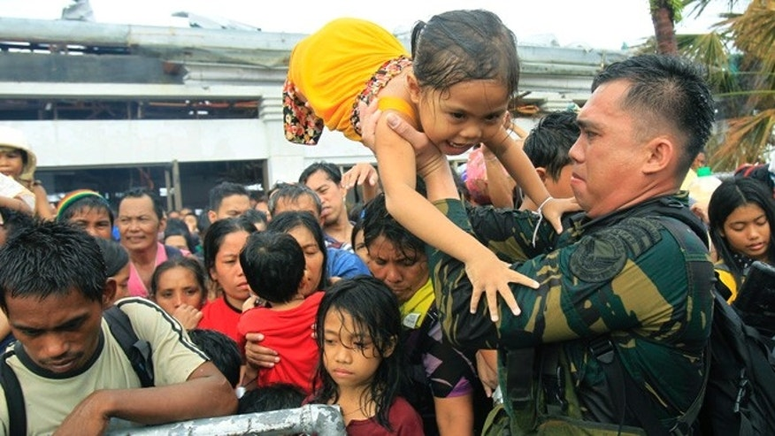 Philippine military personnel try to prioritize children and women first as people wait for evacuation flights in Tacloban, central Philippines, Tuesday, Nov. 12, 2013. Thousands of typhoon survivors swarmed the airport here on Tuesday seeking a flight out, but only a few hundred made it, leaving behind a shattered, rain-lashed city short of food and water and littered with countless bodies.  (AP Photo/Wally Santana)