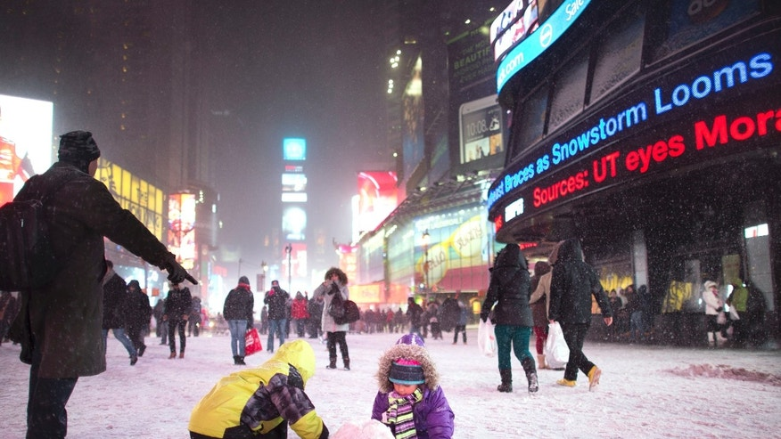 Children make a snow pile in Times Square, during a snowstorm, Thursday, Jan. 2, 2014, in New York. The storm is expected to bring snow, stiff winds and punishing cold into the Northeast. (AP Photo/John Minchillo)