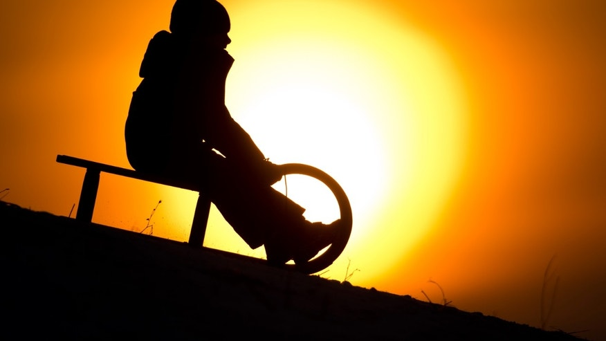 A boy is silhouetted by the setting sun as he slides down a hill near Hannover, northern Germany, Thursday, Jan 30, 2014. (AP Photo/dpa, Julian Stratenschulte)
